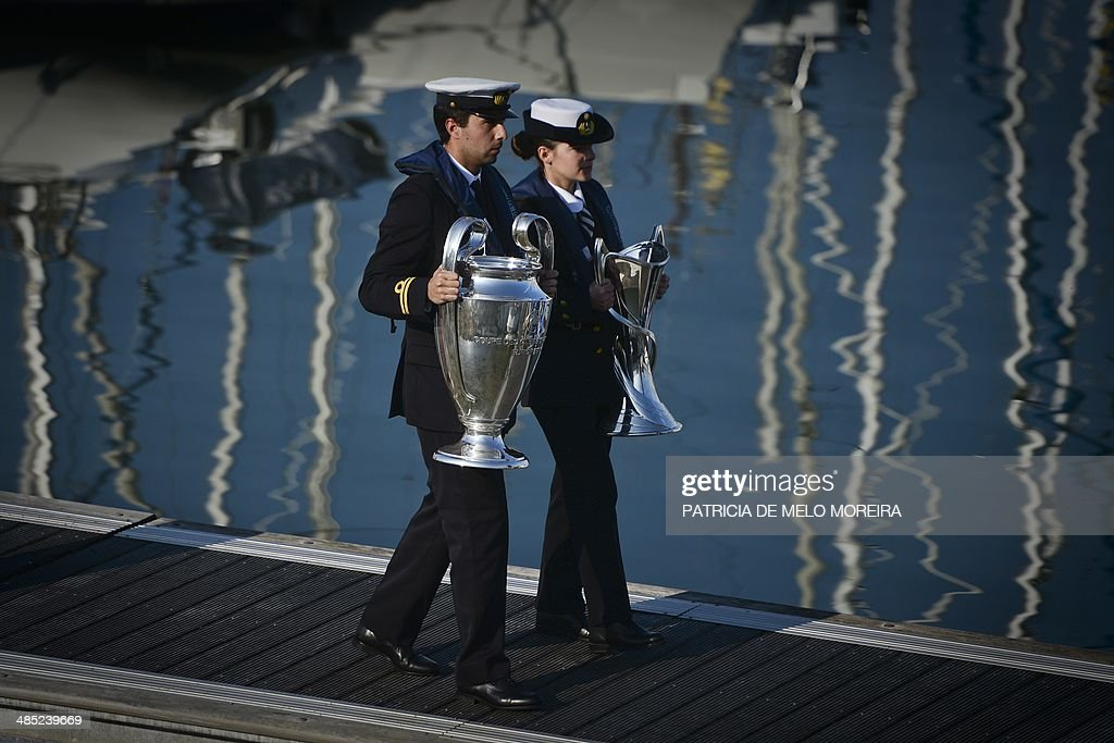 Two sailors hold the UEFA Champions League trophies at Belem's Marina in Lisbon during the UEFA Champions league trophy handover on April 17, 2014. The UEFA Champions League football Final will take place at the Luz Stadium in Lisbon on May 24, 2014.