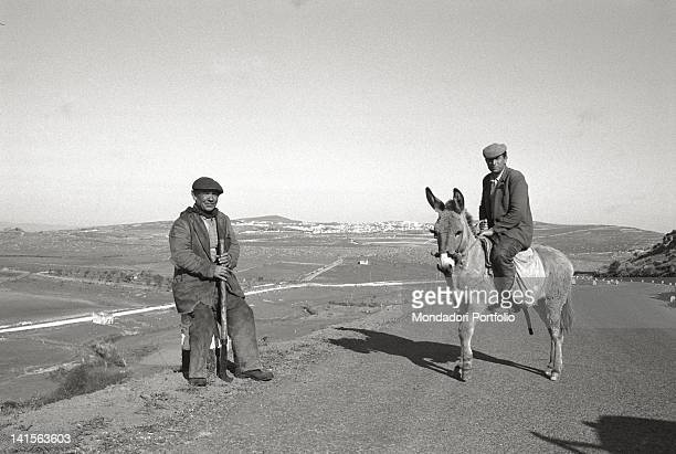 Two Sardinian shepherds on a road on the hills of Barbagia The shepherd on the left is sat down on a road delineator and keeps a sickle tied to a...