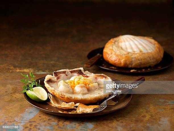 Two scallops baked in shells with vermouth, chervil garnish and lime