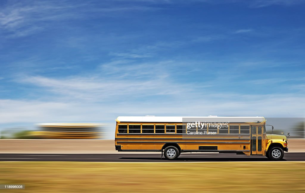 Two school buses on a highway : Stock Photo