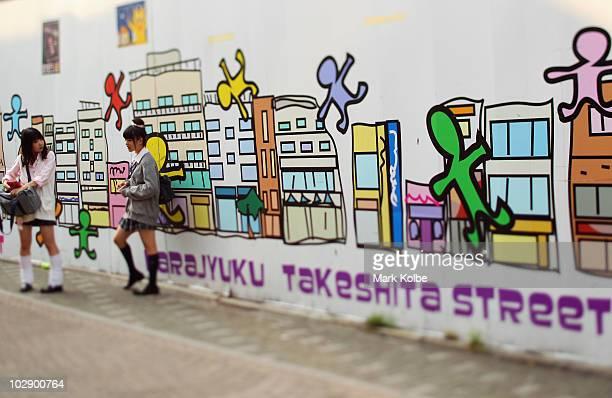 Two school girls stop to talk on Takeshita Street in Harajuku on May 25 2010 in Tokyo Japan Takeshita Street is pedestrianonly shopping strip popular...