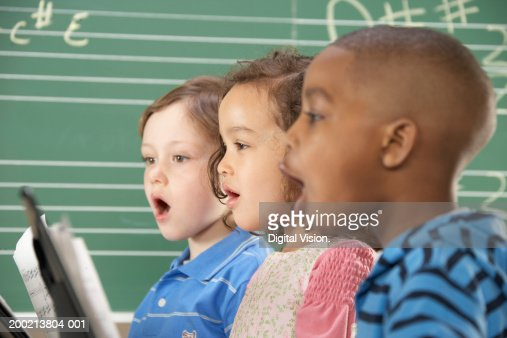 Two schoolboys (5-10) and schoolgirl (5-10) singing in class, close-up : Stock Photo