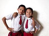 Two schoolboys (9-11) embracing, portrait, close-up