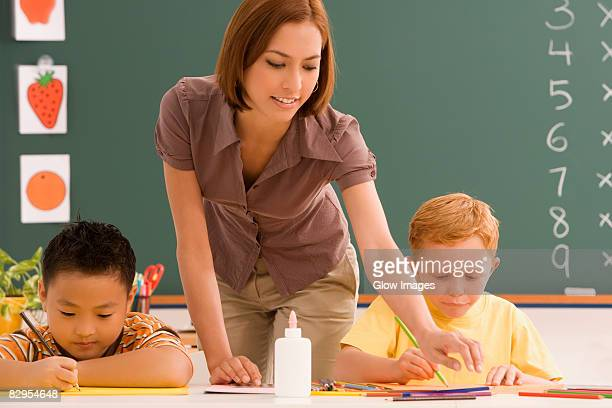 Two schoolboys with their female teacher in a classroom