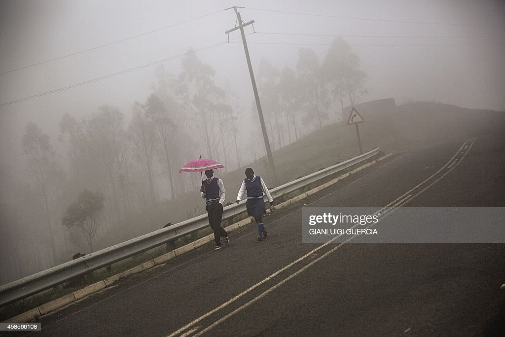 Two schoold children walk in the rain on a hill road through the rural KwaZulu Natal province on the outskirts ot Eshowe South Africa on November 7...