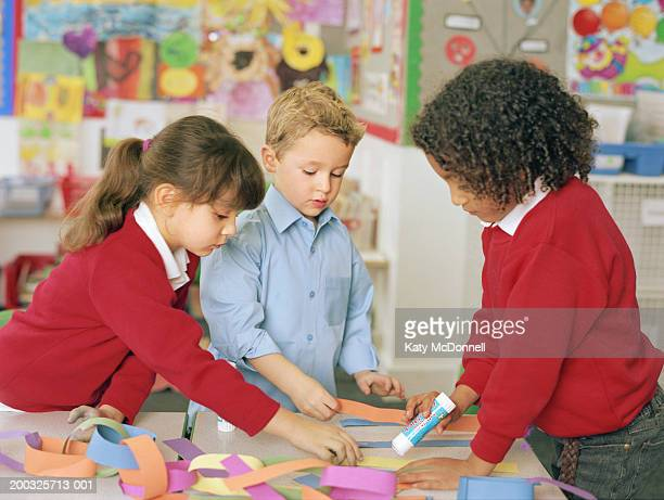 Two schoolgirls and boy (4-6) standing at table making paper chain