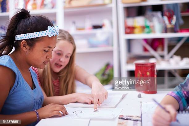 Two schoolgirls discussing in art class