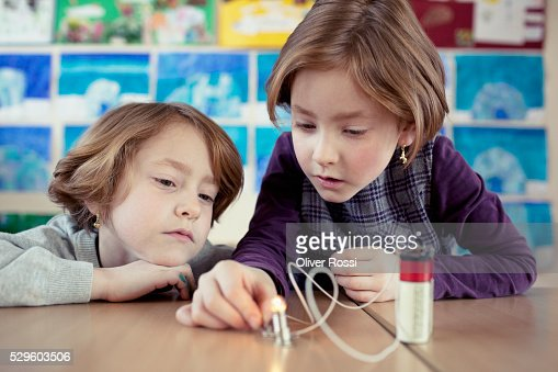 Two schoolgirls (6-7) experimenting with electricity in science class : Stockfoto