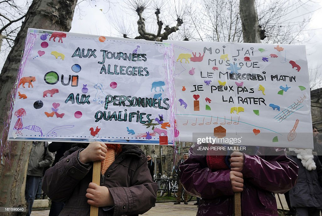 Two schoolgirls hold boards which claim for light schooling rhythms (at left) and to respect of their cultural activities (right) as they demonstrate on February 12, 2013 in Lyon, eastern france, as part of a nationwide strike day over the government's plans to make children attend classes five days a week, instead of the current four. The government recently issued a decree introducing a half day of school on Wednesdays for children 3 to 11 starting in September, while reducing the school day by 45 minutes the rest of the week.