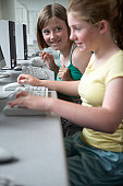 Two schoolgirls (11-13) in computer lesson, smiling