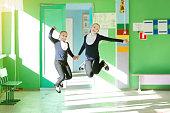 Schoolgirl girls jumping high are having fun at school recess.