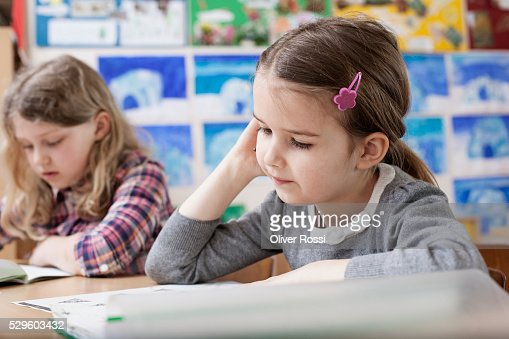 Two schoolgirls (6-7) reading in classroom : Stock Photo