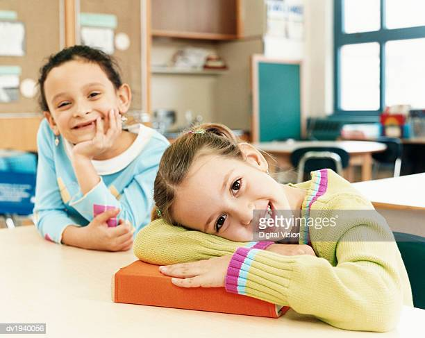 Two Schoolgirls Sitting at Their Desks in a Classroom at Primary School