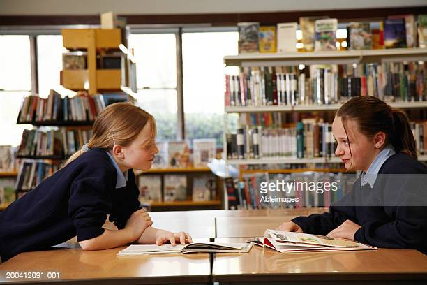 Two schoolgirls (11-13) smiling at each other across table in library