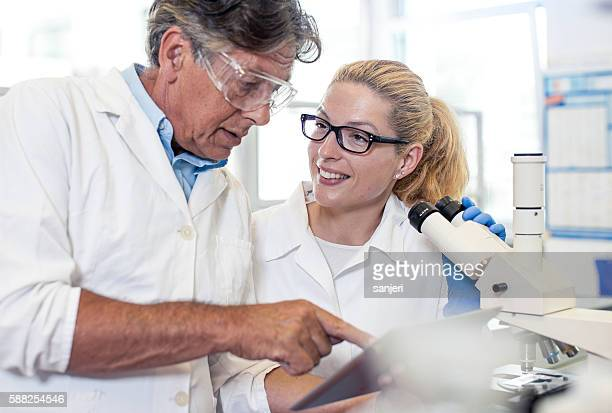 Two Scientists Discussing and Using a Tablet