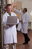 Two scientists making reports in a brewery