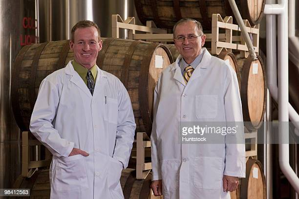 Two scientists standing in a brewery and smiling