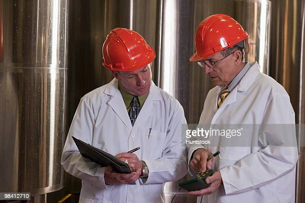 Two scientists with monitoring and record keeping equipment in a chemical plant