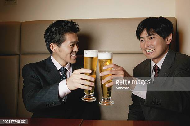 Two seated businessmen toasting beer glasses, smiling