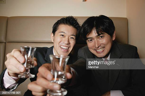 Two seated businessmen toasting glasses, smiling, portrait