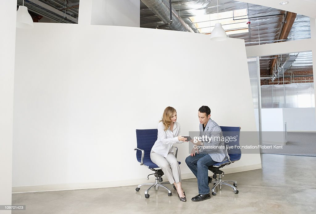 two seated professionals working together : Stock Photo