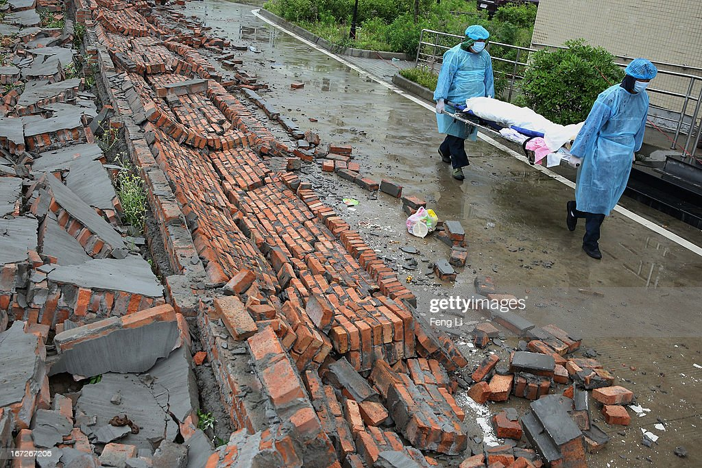 Two security guards carry the dead body of a victims through the ruins at a hospital on April 23, 2013 in Lushan county of Ya An, China. A magnitude 7 earthquake hit China's Sichuan province on April 20 claiming over 190 lives and injuring thousands.