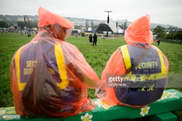 Two security guards look towards the Pyramid stage as revellers gather ahead of the Glastonbury Festival of Music and Performing Arts in Somerset...