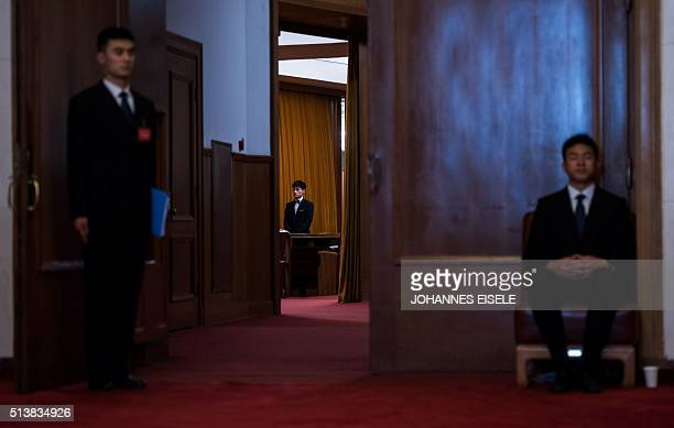 Two security guards stand in front of a door to the Great Hall during the opening ceremony of the National People's Congress in the Great Hall of the...
