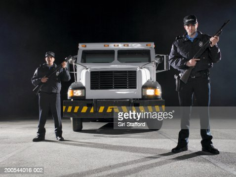 Two security guards standing with guns in front of armored truck