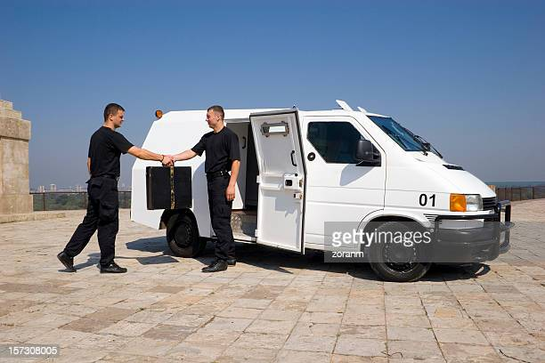 Two security members exchanging a case