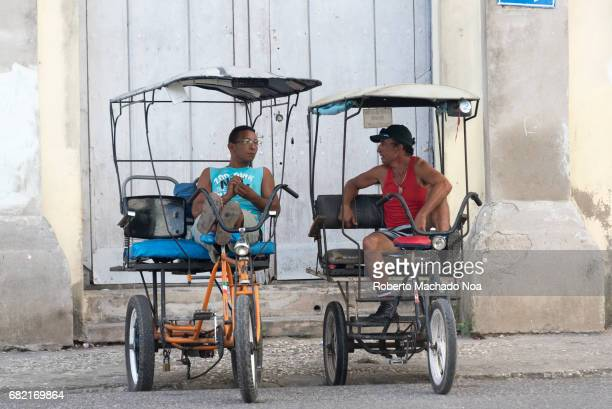 Two self employed men amicably chatting in tricycles or 'bicitaxis' Typical Cuban weathered colonial architecture as background