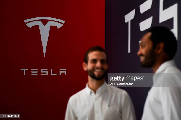 Two sellers stand in front of a logo of the electric carmaker Tesla at a showroom of El Corte Ingles store in Lisbon on September 1 2017 / AFP PHOTO...
