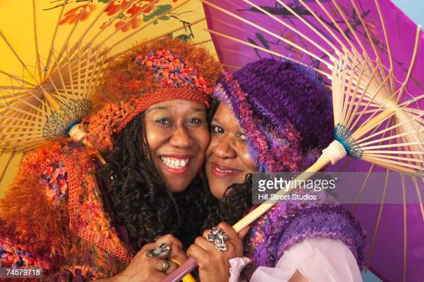 Two senior African women holding parasols