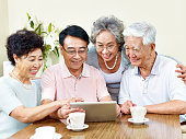 two senior asian couple looking at tablet computer, happy and smiling
