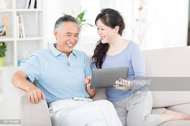 Two senior asian people with digital tablet