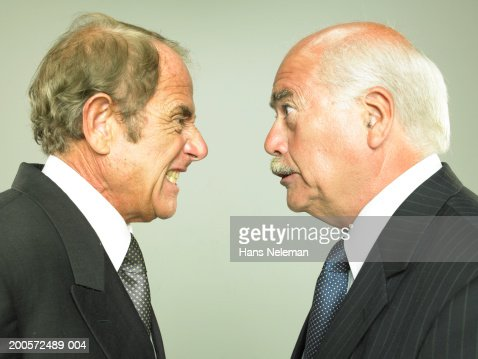 Two senior business men face to face, yelling, studio shot : Stock Photo