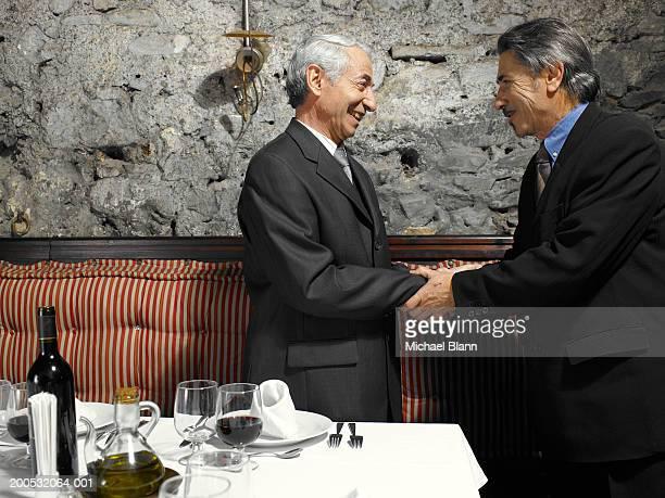 Two senior businessmen shaking hands in restaurant, smiling