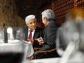 Two senior businessmen talking in restaurant, view across table
