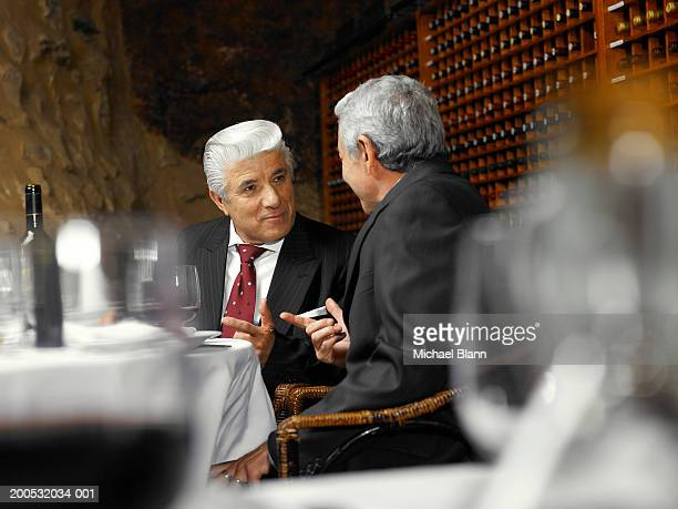 Two senior businessmen talking in restaurant, view across table