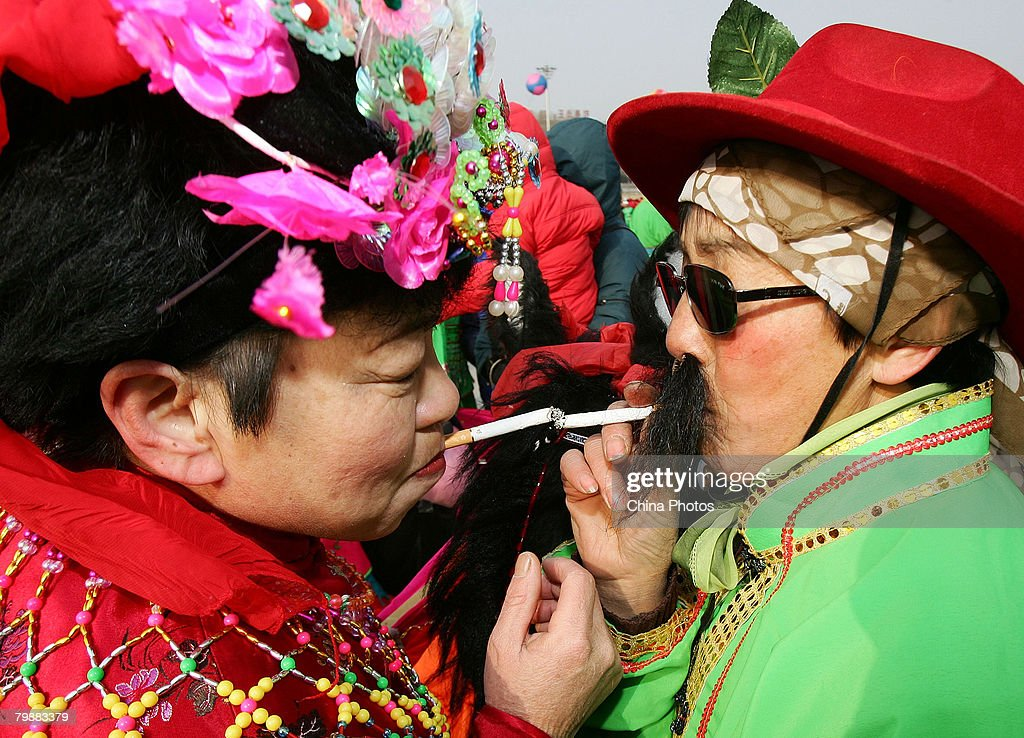 Two senior citizens smoke before a performance to celebrate during Lantern Festival on February 21, 2008 in Changchun of Jilin Province, China. Chinese people have the custom of holding riddle-guessing contests, viewing lanterns and performing stilt-walking to celebrate the Lantern Festival, which fell today, the fifteenth day of the first lunar month.