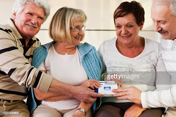 Two senior couple holding pack of  pills in their hands