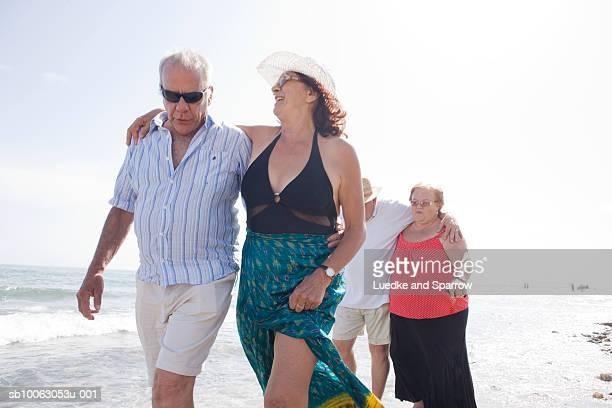 Two senior couples walking on beach