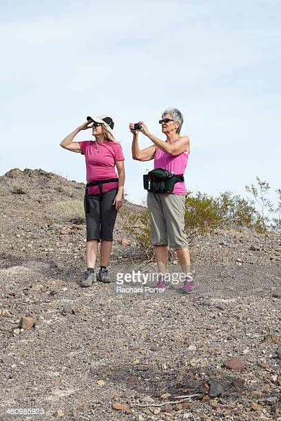 Two senior female hikers looking and photographing view