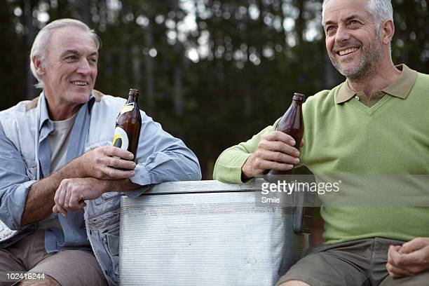 Two senior friends having a beer, smiling