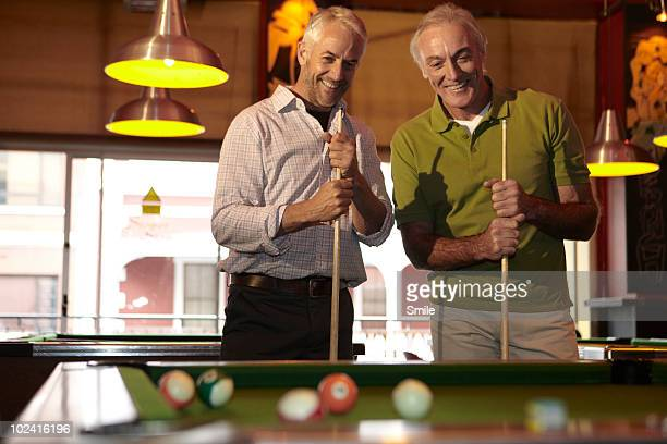 Two senior friends holding pool cues, laughing