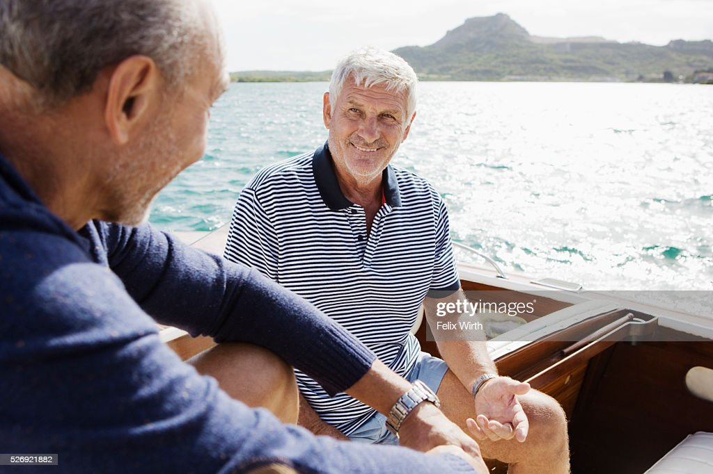 Two senior friends in motorboat : Stock Photo