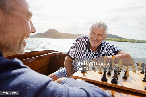 Two senior friends playing chess in motorboat : Stock-Foto