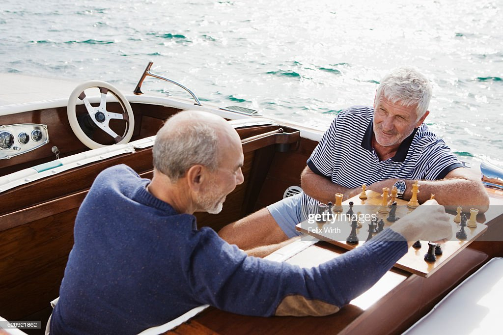 Two senior friends playing chess in motorboat : Photo
