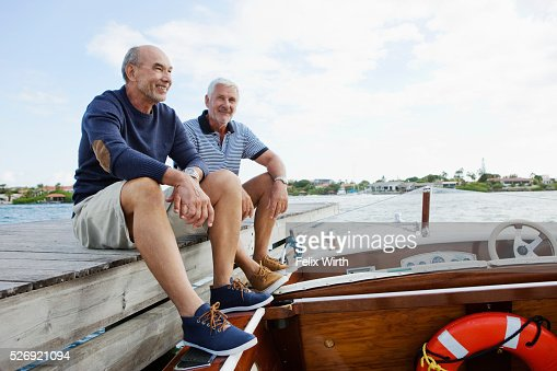 Two senior friends resting on jetty with moored motorboat : Bildbanksbilder