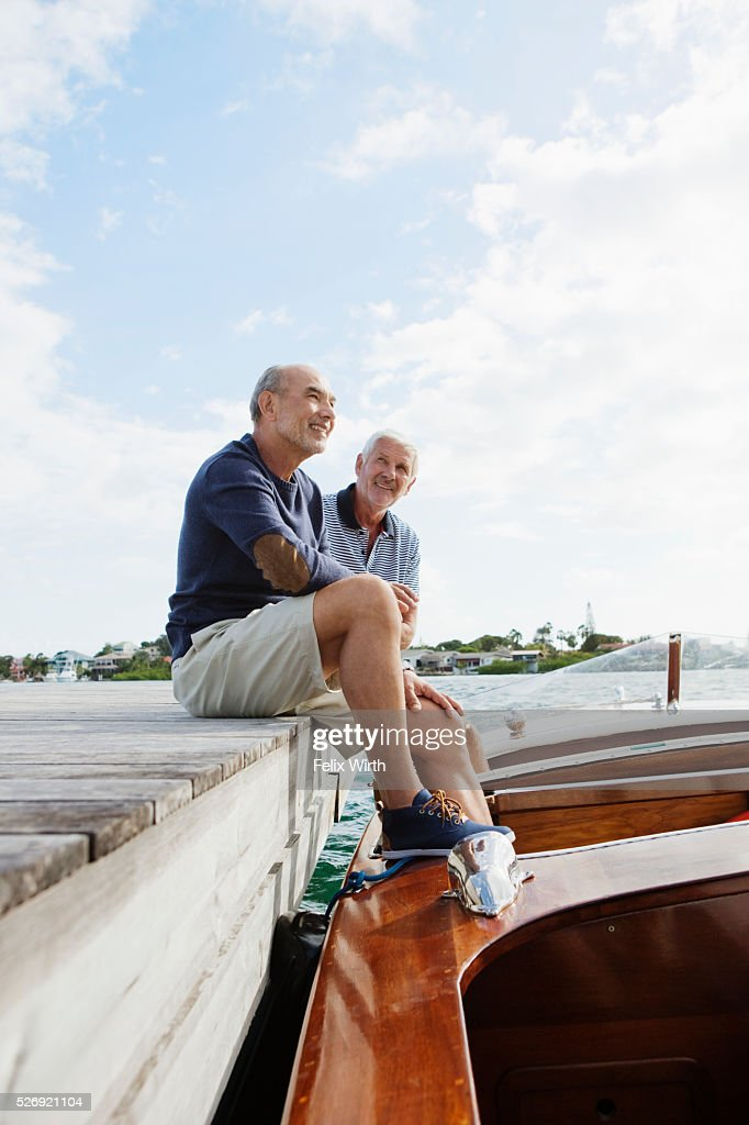 Two senior friends resting on jetty with moored motorboat : ストックフォト